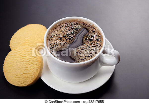 white cup of black coffee with biscuits on a dark background - csp48217655