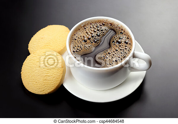 white cup of black coffee with biscuits on a dark background - csp44684548
