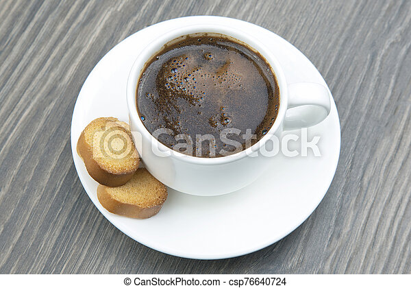 white Cup of black coffee with biscuits on a wooden frame - csp76640724
