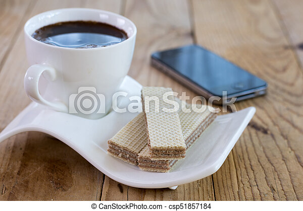 White cup of black coffee with chocolate wafers and mobile in th - csp51857184