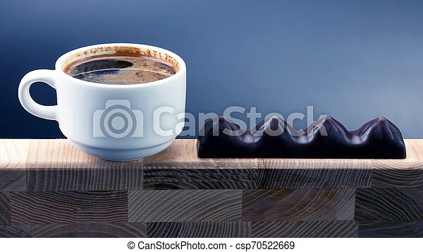 white Cup of black coffee with chocolate on a wooden frame - csp70522669