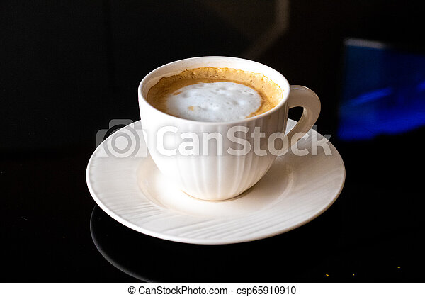 White cup of coffee, saucer on a black background. - csp65910910
