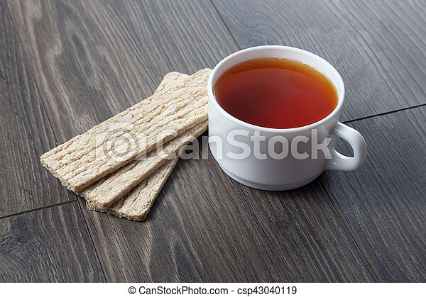 white cup of tea with cookies on a wooden table - csp43040119