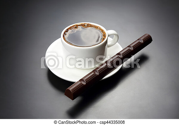 white cup with black coffee and chocolate on the saucer - csp44335008
