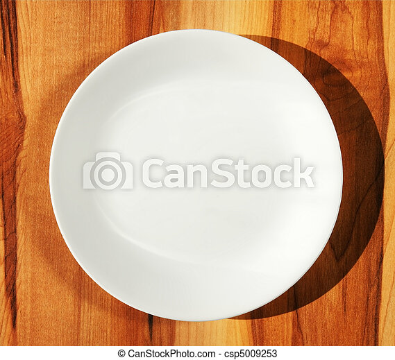 White dinner plate on wood table - csp5009253