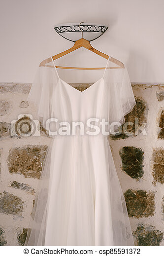 White dress of the bride on a wooden hanger against a stone wall with a sconce. - csp85591372