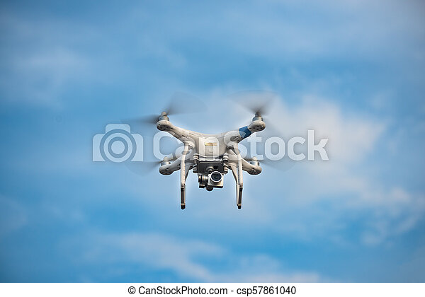 White Drone with Camera Flying in Blue Sky. UAV Concept - csp57861040