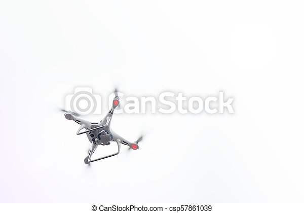 White Drone with Camera Flying in Blue Sky. UAV Concept - csp57861039