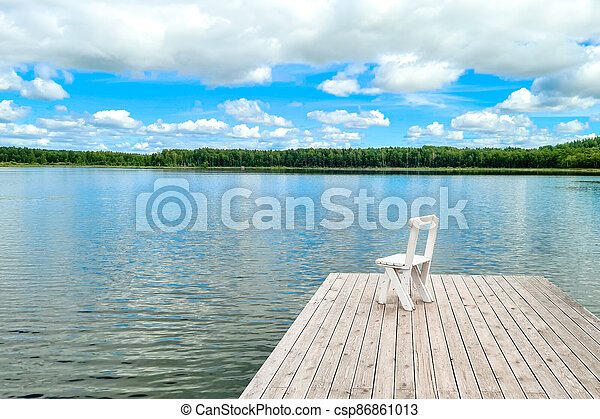 White empty deck chair at the lake dock. - csp86861013