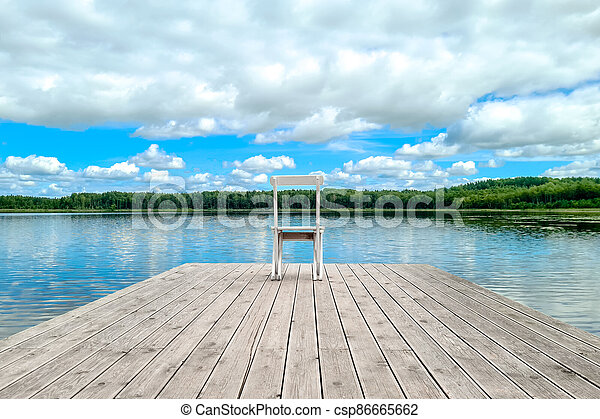 White empty deck chair at the lake dock. - csp86665662