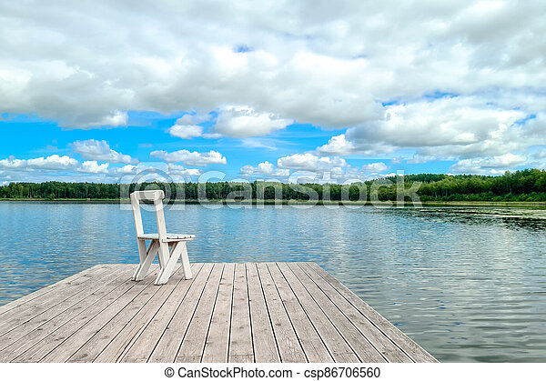 White empty deck chair at the lake dock. - csp86706560