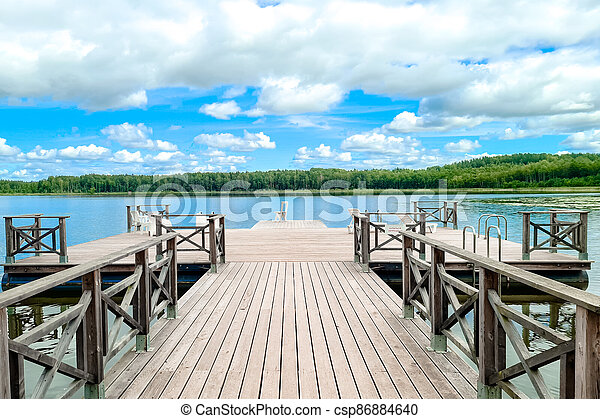 White empty deck chair at the lake dock. - csp86884640