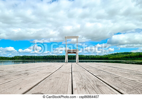 White empty deck chair at the lake dock. - csp86864407