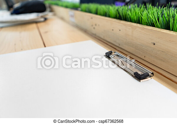 white empty plastic clipboard lay on the wood table. - csp67362568