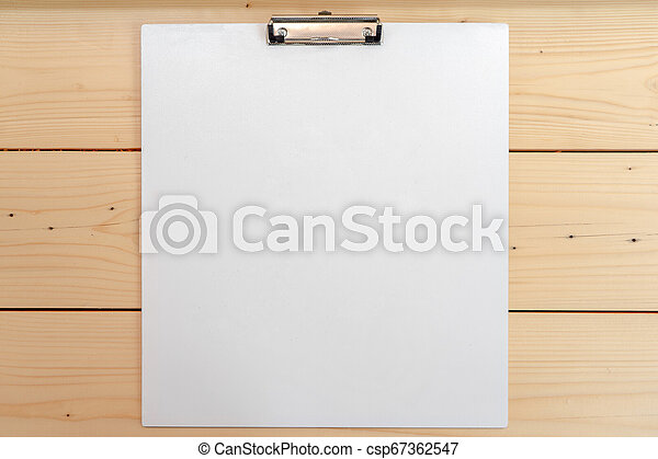 white empty plastic clipboard lay on the wood table. - csp67362547