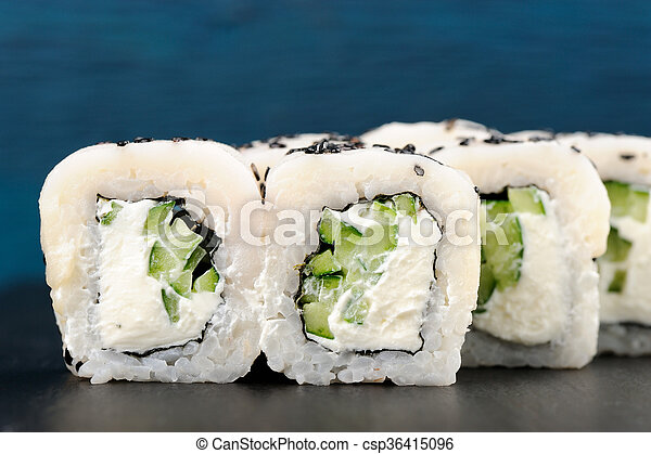 White Fish Cream Cheese Black Sesame Seeds And Cucumber Sushi Rolls On Blue Background