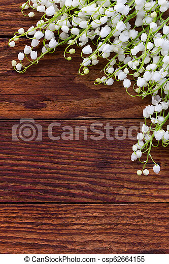 white flowers lilies of the valley scattered on the old wooden brown background. with space for text - csp62664155