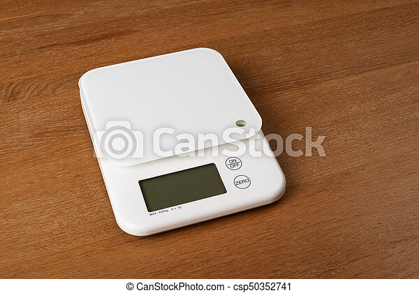 white food scales on a wooden table - csp50352741