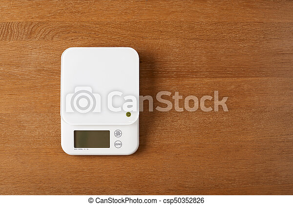 white food scales on a wooden table - csp50352826
