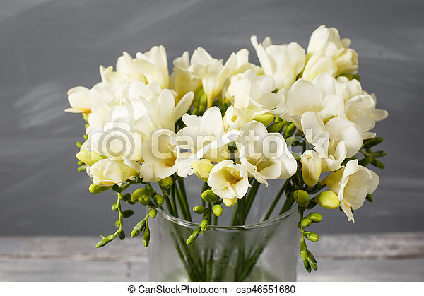 White freesia flowers in decorative vase on a background of gray wall mightylinksfo