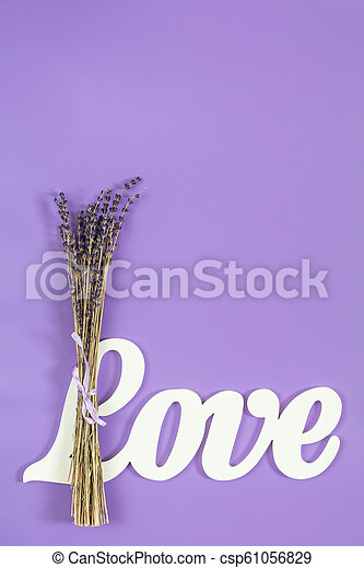 White letters forming word LOVE written with beautiful dried lavender bouquet on violet surface - csp61056829