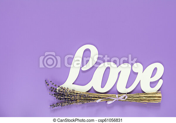 White letters forming word LOVE written with beautiful dried lavender bouquet on violet surface - csp61056831