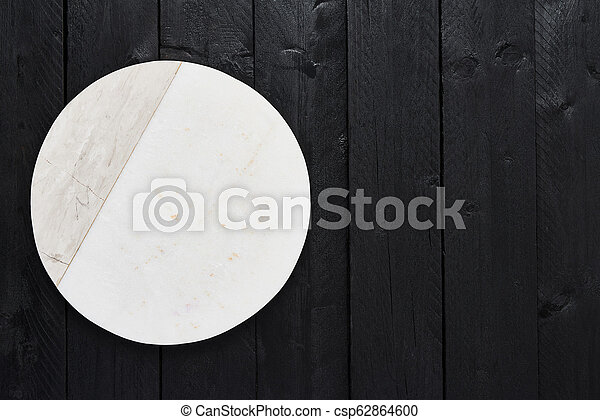White marble serving plate on black wooden table - csp62864600