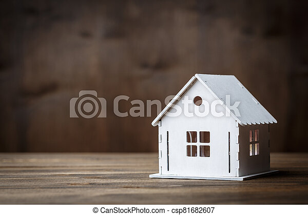 White model of a house with triangle roof on a brown wooden background. - csp81682607