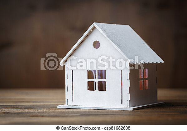 White model of a house with triangle roof on a brown wooden background. - csp81682608