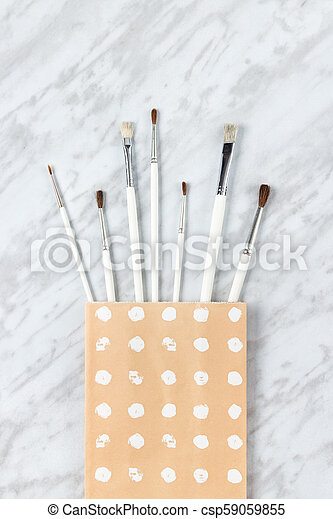 White paint brushes in a decorative paper bag - csp59059855