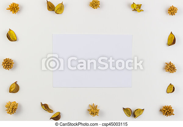 White paper sheet surrounded by yellow dried flowers, plants border frame on white background. Top view, flat lay. - csp45003115