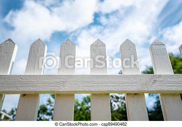 White picket fence under a blue sky - csp89490482
