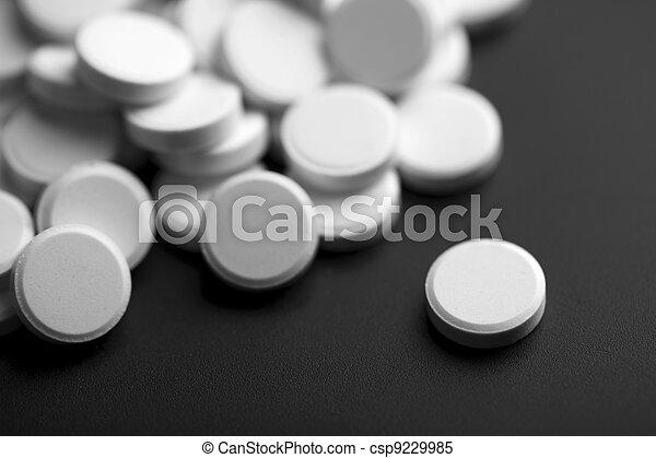 white pills over black background - csp9229985