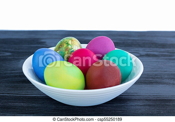 White plate of Easter multicolored eggs on black wooden background - csp55250189