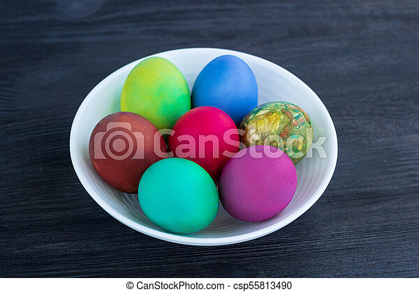 White plate of Easter multicolored eggs on black wood - csp55813490