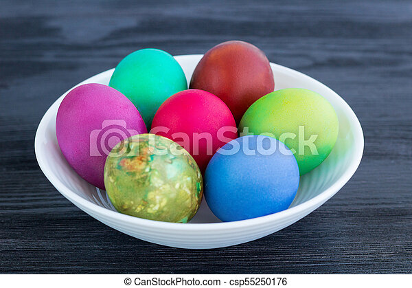 White plate of Easter multicolored boiled eggs on black wood - csp55250176