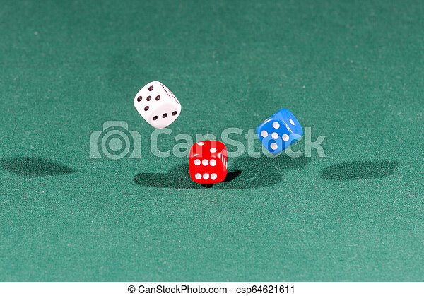 White, red and blue dices falling on a green table - csp64621611