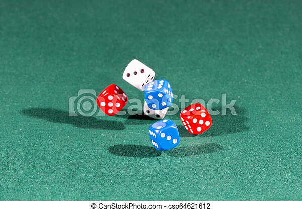 White, red and blue dices falling on a green table - csp64621612