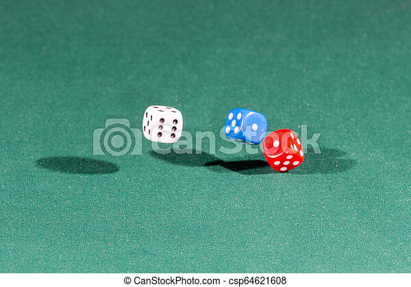 White, red and blue dices falling on a green table - csp64621608