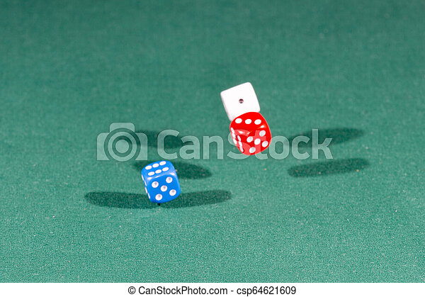 White, red and blue dices falling on a green table - csp64621609