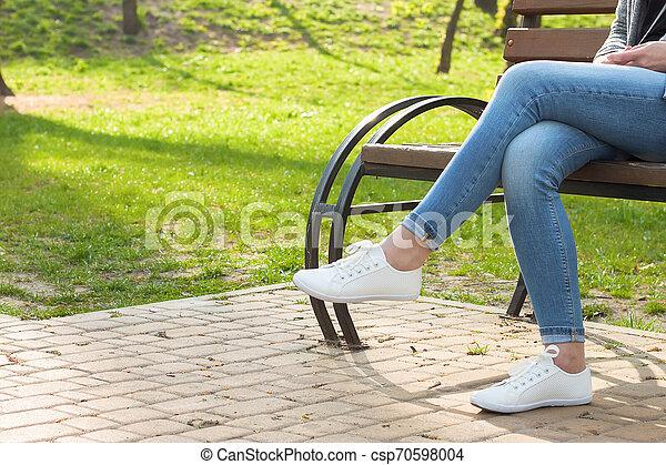 girl legs in blue jeans. White sneakers