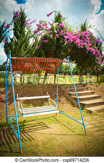 White swing bench for relaxation in the flower garden in summer - csp69714236