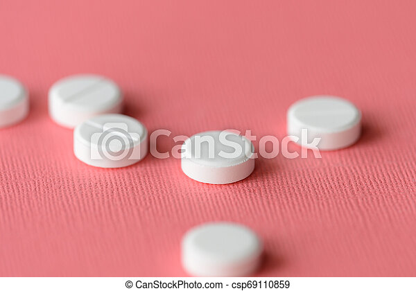 White tablets scattered on a pink background close up - csp69110859