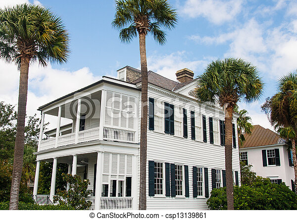 White Traditional Two Story with Black Shutters and Palm Trees - csp13139861