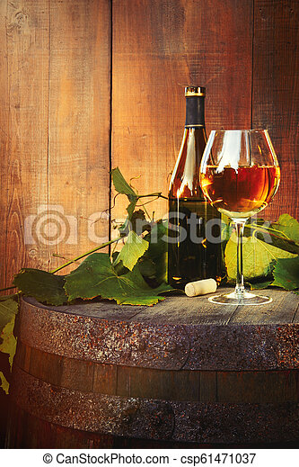 White wine bottle and glass on old barrel - csp61471037