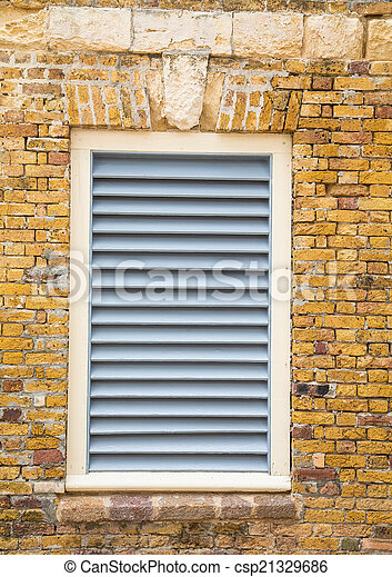 White Wood Shutters in Old Brick Wall - csp21329686
