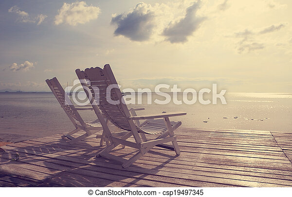 White wooden beach chair facing seascape,vintage filter effect - csp19497345