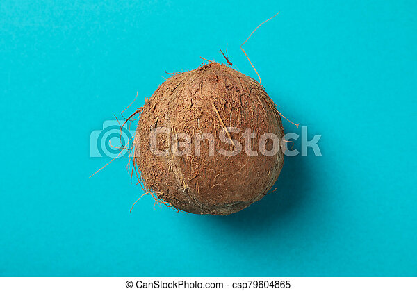 Whole coconut on blue background, top view - csp79604865