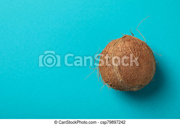 Whole coconut on blue background, top view - csp79897242