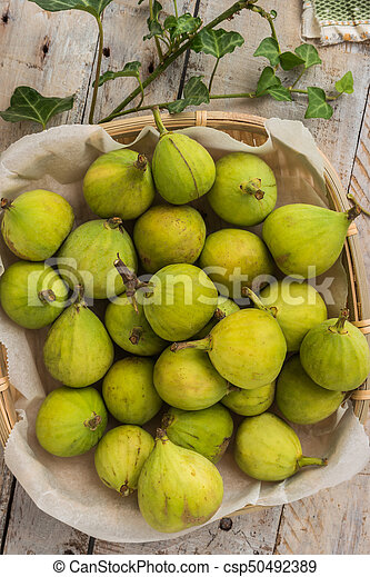 Whole figs in wicker basket on top of a rustic wooden table. - csp50492389